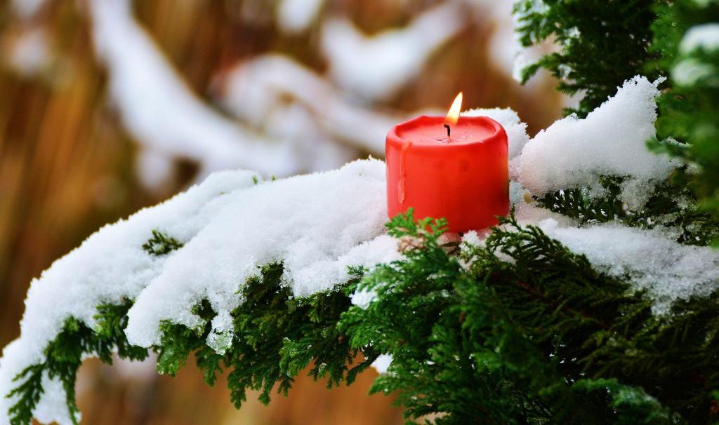 Brennende rote Kerze auf schneebedecktem Zweig | Foto: pixabay/congerdesign